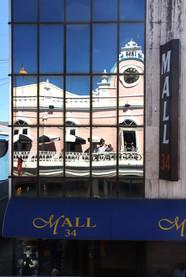 Enfrente de la balconada hay un mall con un cristalera. En la cristalera se refleja la Balconada y el edificio en el que está.