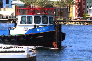 La embarcación que pasa el la lancha de los prácticos
