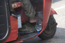 Un detalle del conductor del tuc-tuc: pies descalzos y botella boca abajo