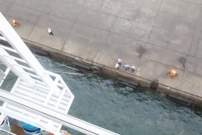 Los trabajadores que van a recoger los cabos de nuestro barco y atarlos al muelle