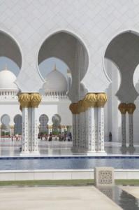 Un estanque cercano, una columnas blancas con capiteles dorados y motivos florales en sus cuerpos cilíndricos y al fondo cúpulas blancas...