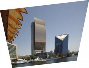 Primer plano a la izquierda: toldo del dhow. Enfrente: edificio color cobre: Banco Nacional; trinagular: Cámara de Comercio