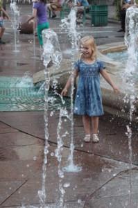 la niña está calculando los tiempos para correr por la fuente y no mojarse