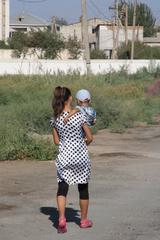 Mujer con niño fuera de la muralla