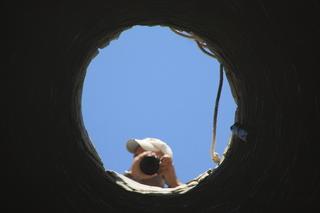 Con el teleobjetivo, nuestra propia imagen reflejada en el fondo del pozo