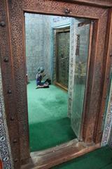 Señora rezando ante la tumba
