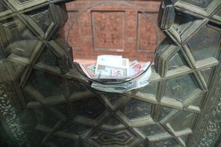 Al fondo el ataud de Pakhlavan Makmud. En primer plano el diner que los fieles dejan