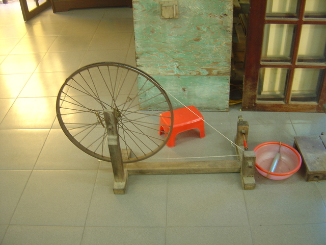 Máquina de hilar hecha con una rueda de bicicleta.