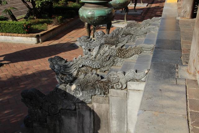 Dragones en la escalera. Al fondo una urna funeraria.