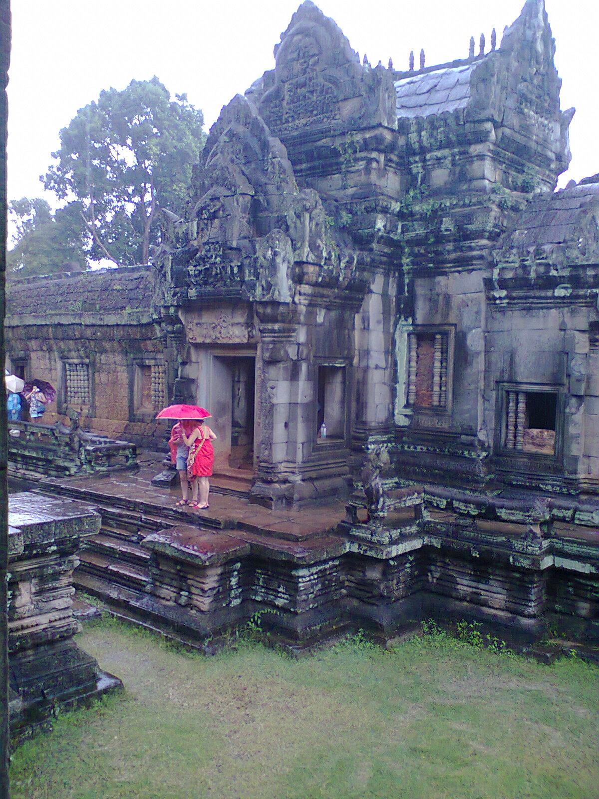 Llueve y el paraguas y su vestido rojo de una compañera de viaje  dan un tque de color