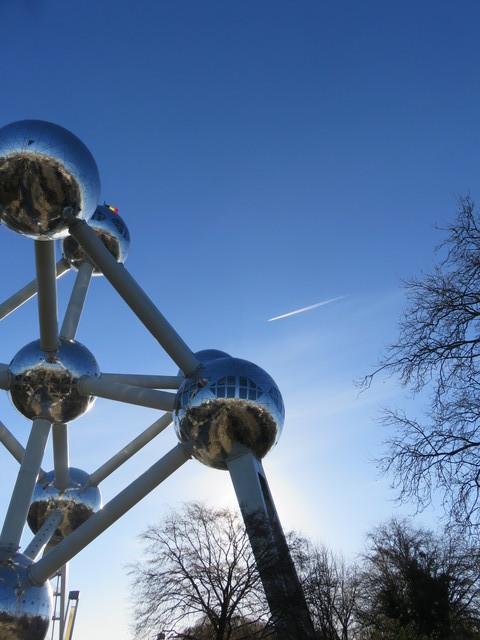 Un avión sobrevuela el Atomium